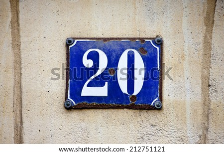 A plaque depicting the number 20 on a rough textured wall.