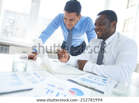 African-american businessman pointing at laptop screen while explaining project to his colleague #212781994