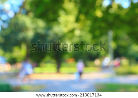 Defocused background of summer park with walking people