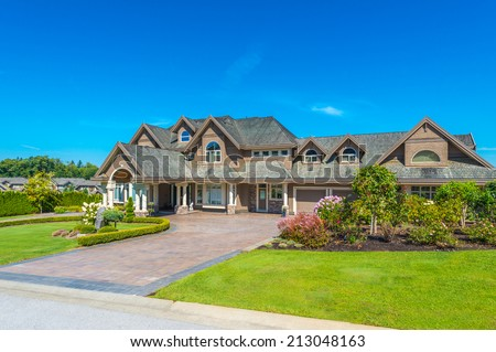 Big custom made luxury house with nicely landscaped front yard and paved driveway to garage in the suburbs of Vancouver, Canada. #213048163