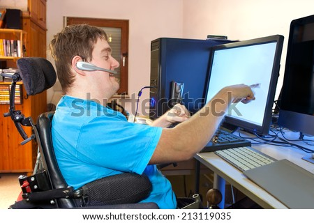 A young man with infantile cerebral palsy caused by a complicated birth sitting in a multifunctional wheelchair using a computer with a wireless headset reaching out to touch the touch screen Royalty-Free Stock Photo #213119035