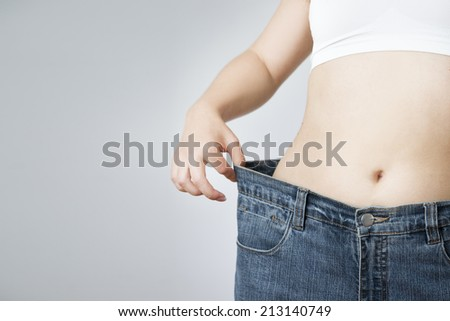 The concept of weight loss. Beautiful slender female body. Young woman in jeans large size. #213140749
