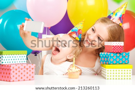 happy children's birthday. selfie. mother photographed  her daughter the birthday child with balloons, cake, gifts