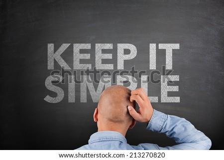 Keep It Simple Concept on Blackboard and businessman scrathing head #213270820