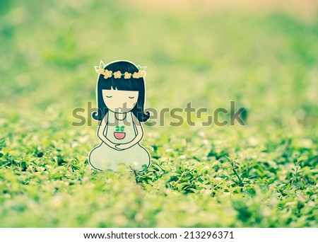 Cute little girl meditating on green grass ,creative design paper cut.