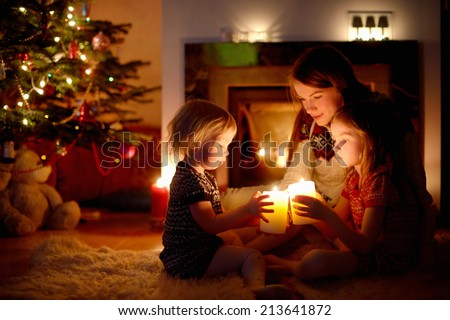 Young mother and her two little daughters sitting by a fireplace holding candles in a cozy dark living room on Christmas eve #213641872