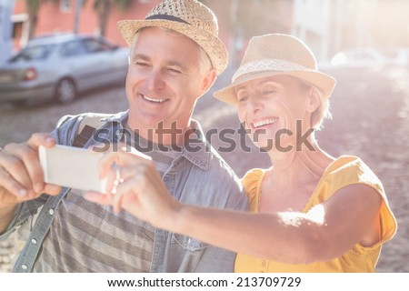 Happy mature couple taking a selfie together in the city on a sunny day #213709729
