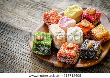 Turkish delight on a dark wood background. toning. selective focus on the white delight. Royalty-Free Stock Photo #213712405