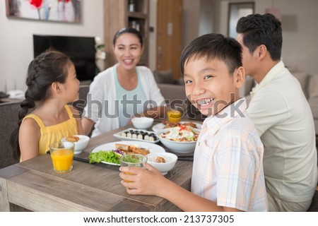Happy Vietnamese boy with a glass of orange juice at the family dinner table #213737305