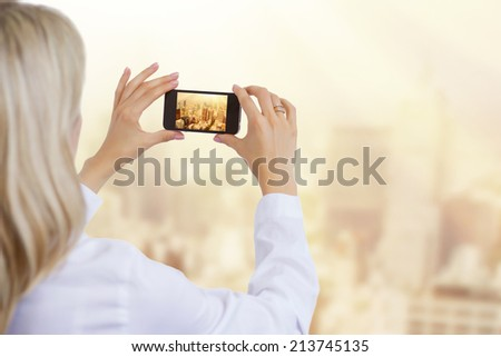 Woman taking photo of city in morning light, business and successful corporate career concept.