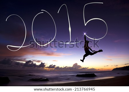 happy new year 2015.young man jumping and drawing 2015 by flashlight Royalty-Free Stock Photo #213766945