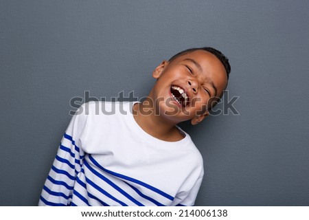 Close up portrait of a happy little boy smiling on gray background  #214006138