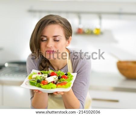 Young housewife enjoying greek salad #214102036