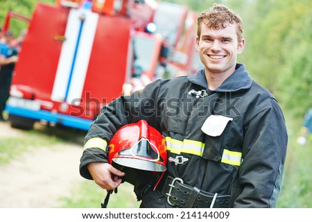 young smiling fireman firefighter in uniform in front of fire engine machine #214144009