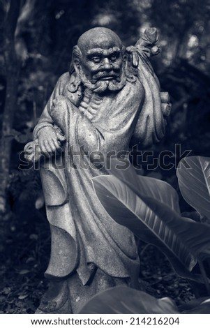 Old ruined Arhat Kanakbharadvaja statue in forest, Taiwan, Asia. #214216204