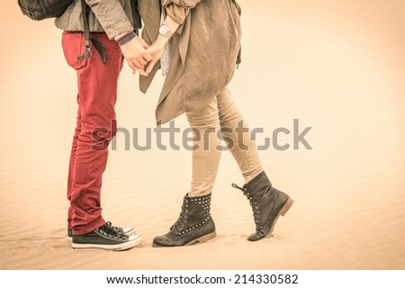 Concept of love relationship in autumn - Couple of young lovers kissing outdoors with closeup on legs and shoes - Desaturated nostalgic filtered look