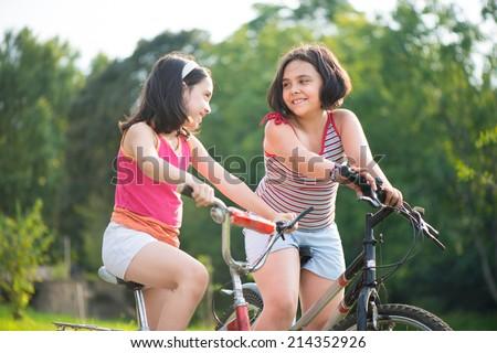Two pretty hispanic children riding on their bikes