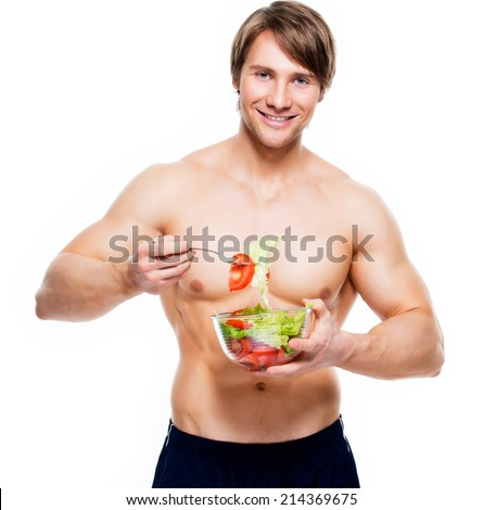 Young happy muscular man eating a salad over white background. #214369675