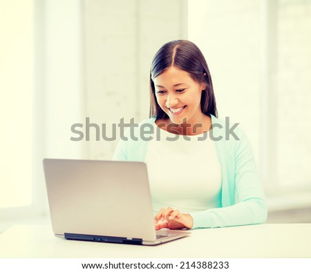 education concept - smiling international student girl with laptop at school #214388233