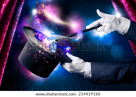 Magician hand with magic wand and hat Royalty-Free Stock Photo #214419160