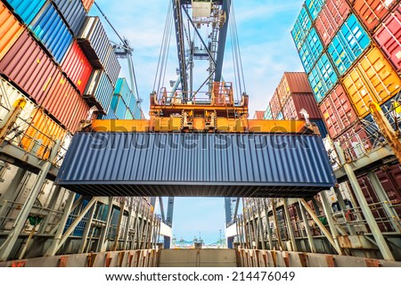Container loading in a Cargo freight ship with industrial crane. Container ship in import and export business logistic company. Industry and Transportation concept. Royalty-Free Stock Photo #214476049