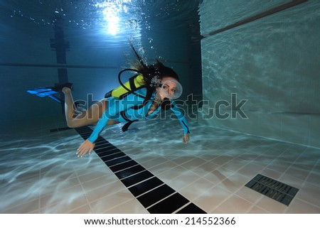 Female scuba diver with lycra suit swimming underwater in the pool  #214552366