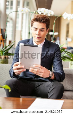 Businessman using tablet PC at the hotel lobby. #214821037