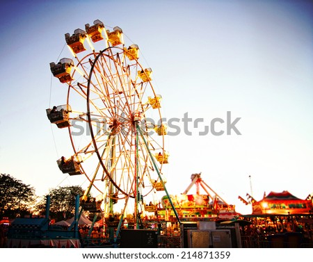a fair ride during dusk on a warm summer evening Royalty-Free Stock Photo #214871359