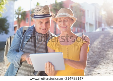 Happy tourist couple using tablet pc in the city on a sunny day #214955167
