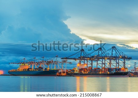Container Cargo freight ship with working crane bridge in shipyard at dusk. #215008867