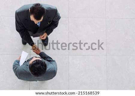 Business partners shaking hands as a symbol of unity, view from the top Royalty-Free Stock Photo #215168539
