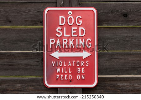 Funny sign. Dog sled parking - Violators will be peed on