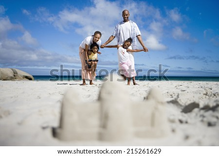 Sandcastle on beach, focus on two generation family in background, portrait, surface level #215261629