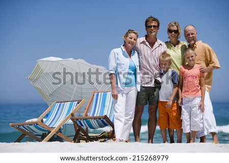 Multi-generational family standing on beach beside deckchairs, smiling, front view, portrait #215268979