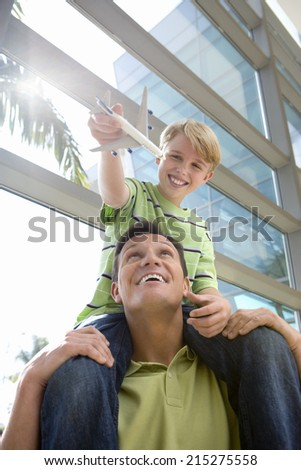 Father carrying son (8-10) on shoulders in airport, boy holding toy aeroplane, smiling, front view, low angle view (lens flare) #215275558