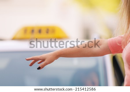 Woman raising her arm to call a taxi. Woman's arm in the focus area, detail of car with taxi sign in the background.  #215412586