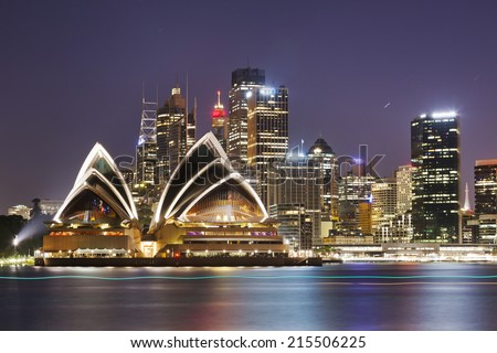 Australia SYdney City CBD close up view over harbour waters at sunset dark sky and reflections of city lights in blurred water Royalty-Free Stock Photo #215506225