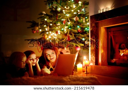 Young mother and her two little daughters reading a book by a Christmas tree in cozy living room in winter #215619478