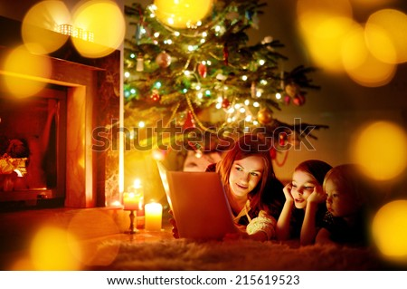 Young mother and her two little daughters reading a book by a Christmas tree in cozy living room in winter #215619523