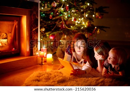 Young mother and her daughters using a tablet pc by a fireplace on warm Christmas evening #215620036
