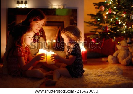 Young mother and her two little daughters sitting by a fireplace holding candles in a cozy dark living room on Christmas eve #215620090