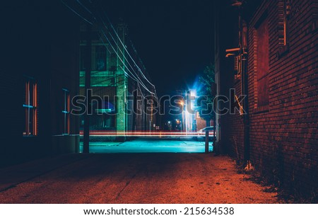 Dark alley and light trails in Hanover, Pennsylvania at night. Royalty-Free Stock Photo #215634538