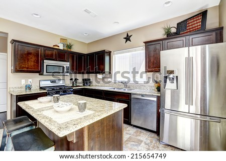 Dark brown cabinets with granite tops. Kitchen island with stools #215654749