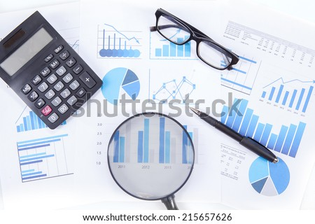 High angle view of magnifying glass with business chart, calculator, glasses, and pen #215657626