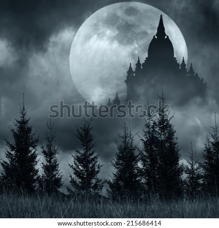 Magic castle silhouette over full moon at mysterious night. Fantasy background with pine tree forest under dramatic cloudy sky