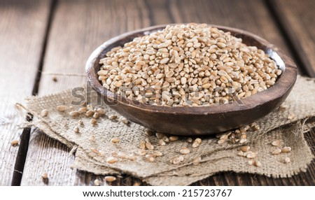 Portion of Wheat Grains (close-up shot) on dark wooden background #215723767