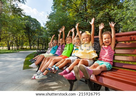 Group of kids on the bench cheering lifting hands #215926795