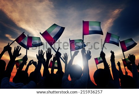Group of People Waving Flag of UAE in Back Lit Royalty-Free Stock Photo #215936257