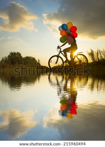 Symbol of easy birthday celebration peace tranquility Young Girl in dress with sunglasses riding bicycle flying air balloons on leash yellow sun set ray sky background No face Unrecognizable person