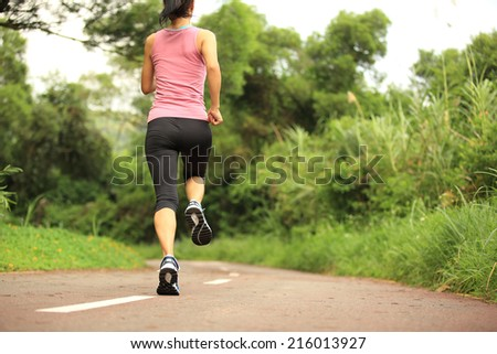 Runner athlete running on forest trail. woman fitness jogging workout wellness concept.  #216013927